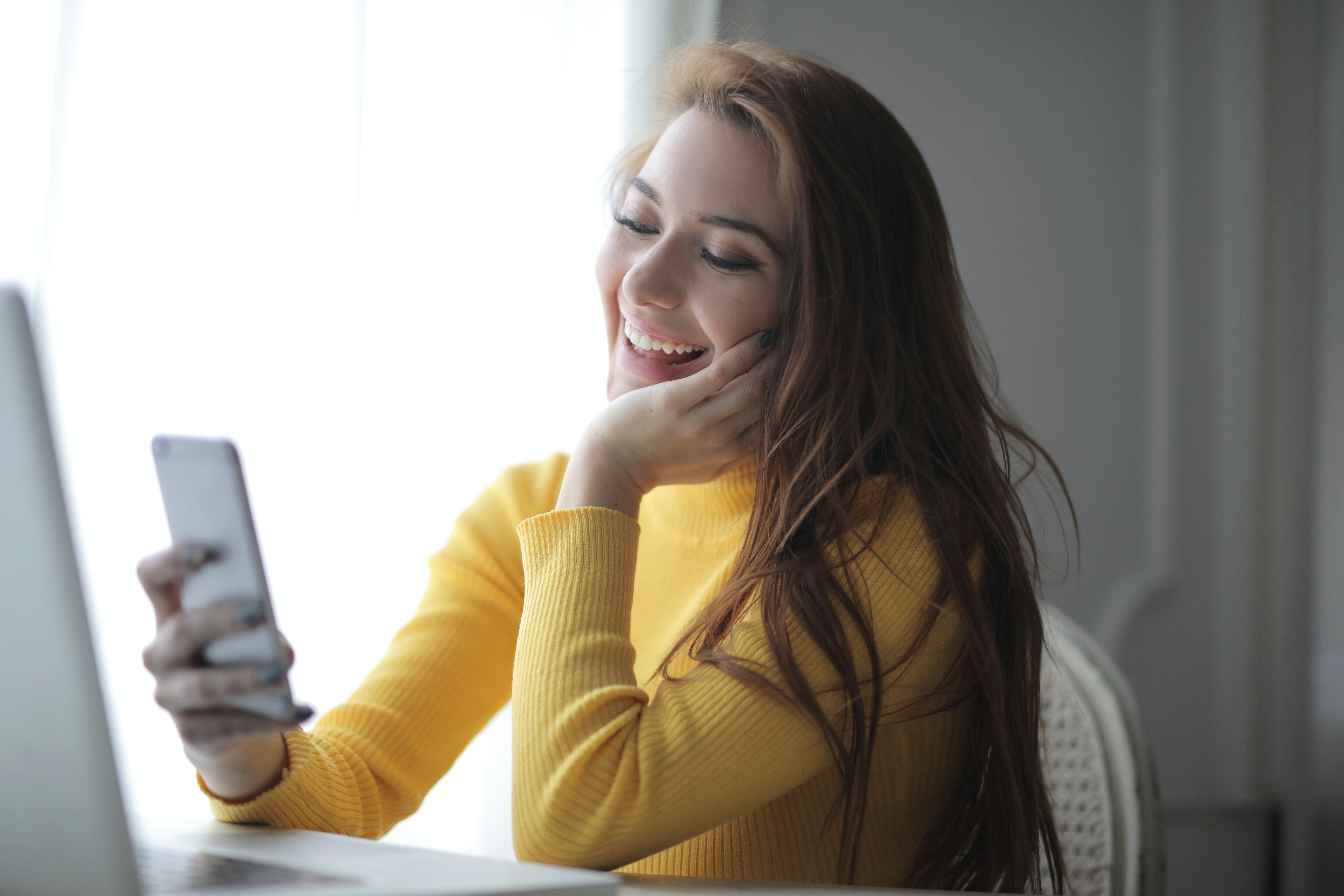 cheerful-young-female-student-using-smartphone-while-working-3884194