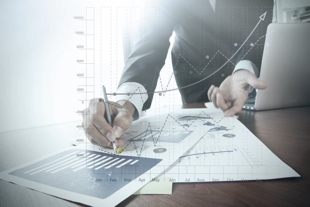 close up of businessman hand working on laptop computer with business graph information diagram on wooden desk as concept